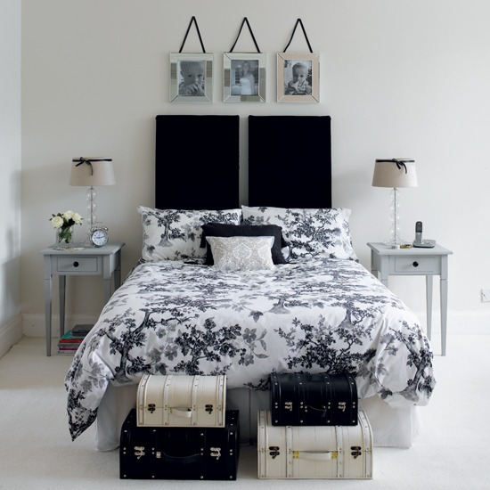 Black duvet covers serve as a focal point in the white bedroom.
